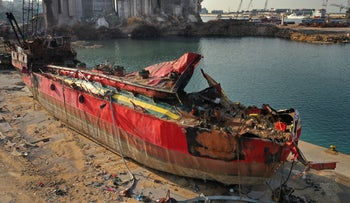 A destroyed ship lies near towering grain silos gutted in the massive August explosion at the Beirut port, last year.