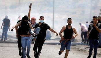 An injured Palestinian demonstrator gestures as he is evacuated during clashes with Israeli forces at a protest over tension in Jerusalem and Israel-Gaza escalation, near Hawara checkpoint near Nablus in the Israeli-occupied West Bank, May 14