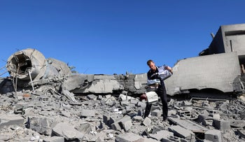 A Palestinian man salvages documents and copies of the Koran from the rubble of the Qlebo mosque at the Jabalia refugee camp in the northern Gaza Strip after Israeli air shelling early on Saturday