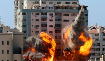 An explosion is seen near a tower housing AP, Al Jazeera offices during Israeli missile strikes in Gaza City, today.