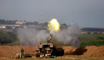 Israeli soldiers fire a self-propelled howitzer towards the Gaza Strip, yesterday.