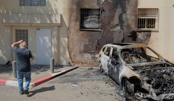 An Israeli man walks past a BMW car which was set ablaze in the middle of the night next to a residential building in Jaffa, a mixed neighborhood of Tel Aviv, yesterday.
