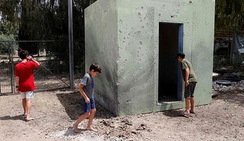 Children at a structure bearing traces of rockets fired from Gaza, Kibbutz Nahal Oz, last month.