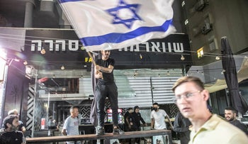 Right-wing Jewish rioters outside of the restaurant where the Arab man was attacked in Bat Yam last week.