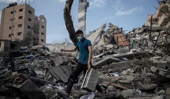 A Palestinian man inspects the damage of a six-story building which was destroyed by an early morning Israeli airstrike, in Gaza City.