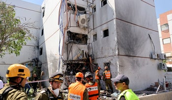 Israel soldiers work at a damaged building following a rocket attack from Gaza, in Ashdod, Israel, yesterday.