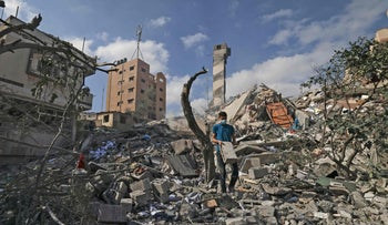 A Palestinian youth looks for salvageable items amid the rubble of the Kuhail building destroyed in an Israeli airstrike on Gaza City this week