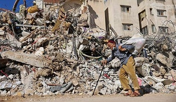 A man walking past a building destroyed by Israeli shelling in Gaza City, Wednesday.