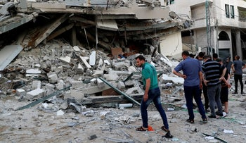 People inspect the rubble of destroyed residential building that was hit by an Israeli airstrike, in Gaza City.