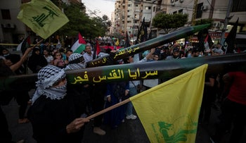 Palestinian members of Islamic Jihad hold replica rockets at a Hezbollah rally in Beirut on Monday.