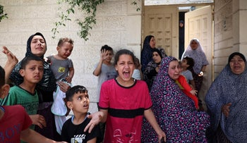 Palestinians women and children evacuating their homes and heading for shelter during an Israeli airstrike in Gaza City, earlier today. (Illustrative)