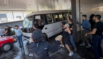Members of the Christian right-wing Lebanese Forces group attack a bus carrying Syrian voters heading their embassy to vote in the presidential elections in the town of Zouk Mosbeh, on Thursday.