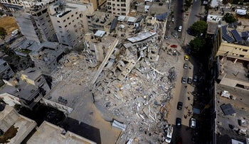 This aerial view taken on May 21, 2021, shows the Al-Shorooq building in Gaza City, that was levelled by an Israeli air strike during the recent military conflict between Israel and the Palestinian enclave ruled by Hamas, after a ceasefire brokered by Egypt. - A ceasefire between Israel and Hamas, the Islamist movement which controls the Gaza Strip, appeared to hold today after 11 days of deadly fighting that pounded the Palestinian enclave and forced countless Israelis to seek shelter from rockets