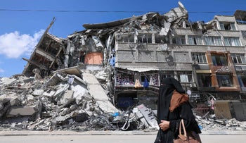 A Palestinian woman walks past a destroyed building in Gaza City, on Saturday.