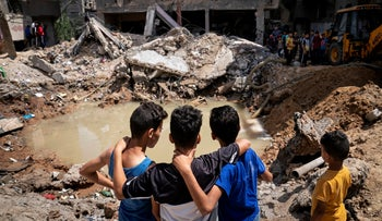 Children gather beside the crater where the home of Ramez al-Masri was destroyed by an airstrike during hostilities between Gaza's Hamas rulers and Israel, today.