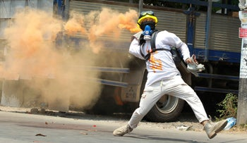 An anti-coup protester throws a smoke bomb against police crackdown in Thaketa township Yangon, in March.