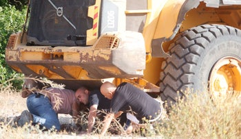 Men taking cover under a vehicle in Ashkelon during a siren warning of rocket fire from Gaza, two weeks ago.