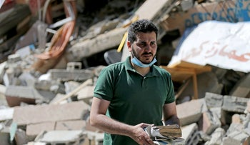 Shaban Esleem collecting books from his bookstore on Monday which was destroyed in Israeli airstrikes.