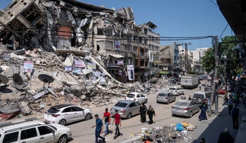Motorists and pedestrians move past a building destroyed by an air-strike prior to a cease-fire that halted the 11-day war between Gaza's Hamas and Israel.
