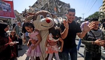 Palestinians wearing cartoon-inspired costumes entertain children on the rubble of al-Shourouk tower, recently destroyed by Israeli strikes, in Gaza City, today
