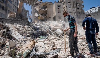 Heavy construction equipment is used to sift through rubble to uncover valuables from the scene of a building destroyed in an airstrike in Gaza.