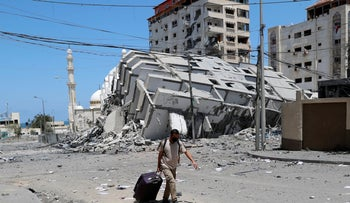 A man pulls his luggage while passing the rubble of a destroyed building which was hit by Israeli airstrikes, in Gaza City, earlier in May.