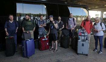 Tourists wait next to a bus outside Ben Gurion International Airport after entering Israel by plane, on Thursday.