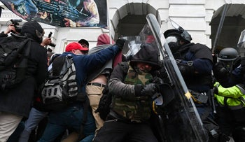 Riot police push back a crowd of Trump supporters after they stormed the Capitol building on January 6.