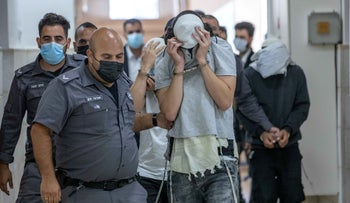 A suspect in the attempted murder of a Palestinian is escorted into court, Sunday.