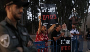 Protesters hold signs reading 'leftists are traitors' outside Ayelet Shaked's home, Monday.