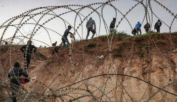 Palestinians going through a barbed-wire fence into Israel as they attempt to reach their workplaces close to the Israeli checkpoint near Hebron in the West Bank, in March.