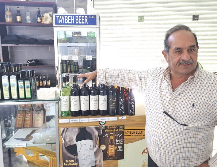 Nadim Khoury with some of the products manufactured by his business in Taybeh, including wine, olive oil and beer.