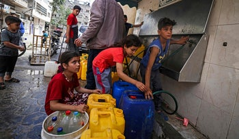 Palestinian children filling plastic containers with water in Gaza, where 95% of the water supply is not potable