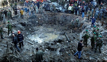 In this Feb. 14, 2005 file photo, rescue workers and soldiers stand around a massive crater after a bomb attack that tore through the motorcade of former Prime Minister Rafik Hariri in Beirut, Lebanon