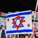 Participants in a pro-Palestinian rally in the borough of Queens, New York City raise a 'Free Palestine' sign, an Israeli flag superimposed with the sights of a gun, and a photo of Saddam Hussein