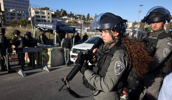 Israeli security forces stand guard to prevent Palestinians from passing through an Israeli Police checkpoint at the entrance of the Sheikh Jarrah neighbourhood in East Jerusalem
