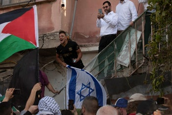 A man holding the Israeli flag shouts at protesters waving the Palestinian flag at the front gate of a home now occupied by Israeli Jews in the Sheikh Jarrah neighborhood of Jerusalem earlier this year