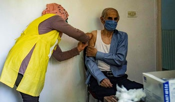 A medic administers a vaccine from the World Health Organization in Qamishli, Syria last week.