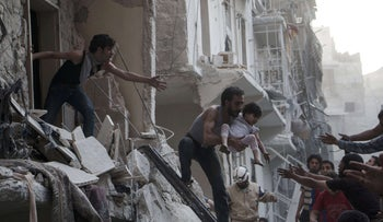 A man evacuates a child from a building following a reported barrel bomb attack by Syrian government forces in Aleppo, Syria, in 2015