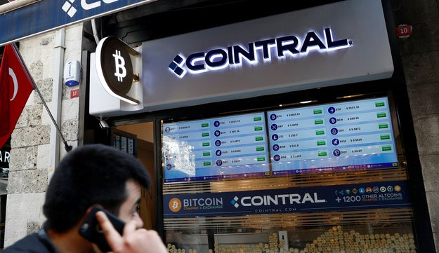 A man talks on his cell phone as he walks past a cryptocurrency exchange store in Istanbul, Turkey, April 27, 2021.