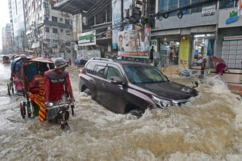 Commuters making their way through a waterlogged street after a heavy downpour in Dhaka, Bangladesh, last year.
