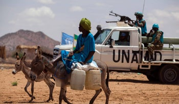 A woman riding a donkey loaded with water jerrycans, while United Nations troops from Tanzania conduct a patrol in the camp for internally displaced persons (IDP) in Khor Abeche, South Darfur, in 2014.