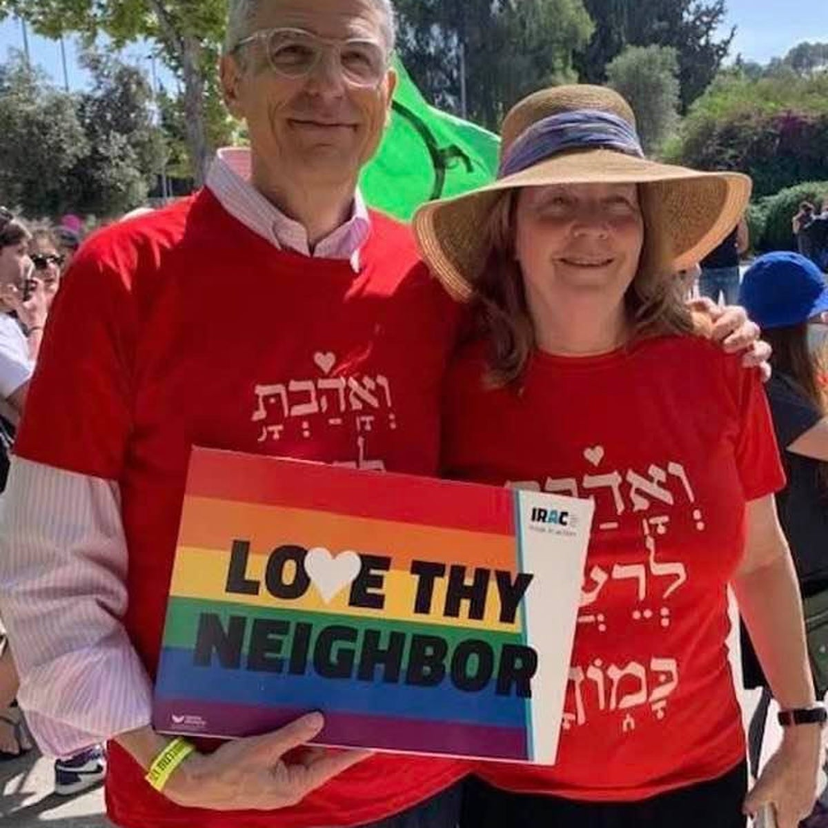 """Rabbi Rick Jacobs and IRAC executive director Anat Hoffman wearing red shirts and holding a rainbow sign that reads """"Love thy neighbor"""" at the Jerusalem Pride Parade in June 2021."""