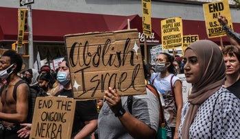 """Protesters at a pro-Palestinian rally in Queens last month. One handwritten placard states """"Abolish Israel."""""""
