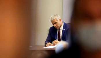 Yair Lapid writing in the Knesset, on Monday.