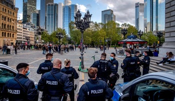 German police officers watch people gathering on the square in front of the Old Opera for drinks and food in Frankfurt, Germany, last month.