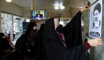 A TV broadcasts the debate of presidential candidates at a campaign center in Tehran, on Saturday.