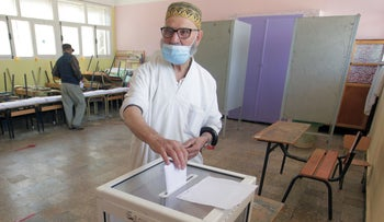 A man casts his vote in a polling station in the country's first legislative elections since the ouster of ex-president Abdelaziz Bouteflika, in Algiers, Algeria, today.