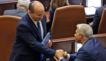 Naftali Bennett shakes hands with Yair Lapid at the Knesset, Sunday.