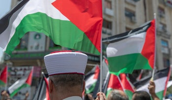 A Palestinian clerk takes part in a flags march in the West Bank city of Ramallah, last week.